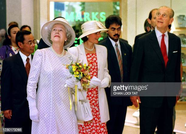 Britain's Queen Elizabeth II and Prince Philip tour the shopping mall at the twin-tower Kuala Lumpur City Centre, the world's tallest buildings 22...
