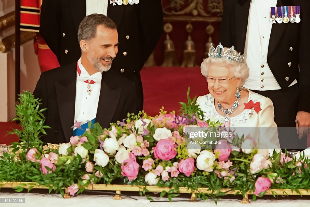 Britain's Queen Elizabeth II (R) and Spanish King Felipe VI chat during a State Banquet at Buckingham Palace in central London on July 12, 2017, on the first day of the Spanish King and Queen's three-day state visit. Spanish King Felipe VI called for a deal on the status of Gibraltar that would be 'acceptable to all' on Wednesday, raising a thorny dispute on the first day of his state visit to Britain. / AFP PHOTO / POOL / Dominic Lipinski