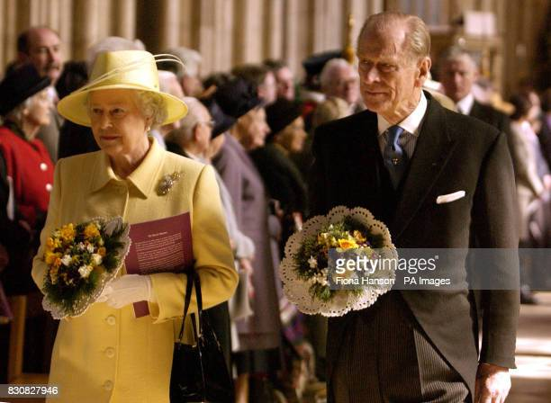 Britain's Queen Elizabeth II and the Duke of Edinburgh carry nosegays historically intended to ward off disease and evil spirits as they leave...