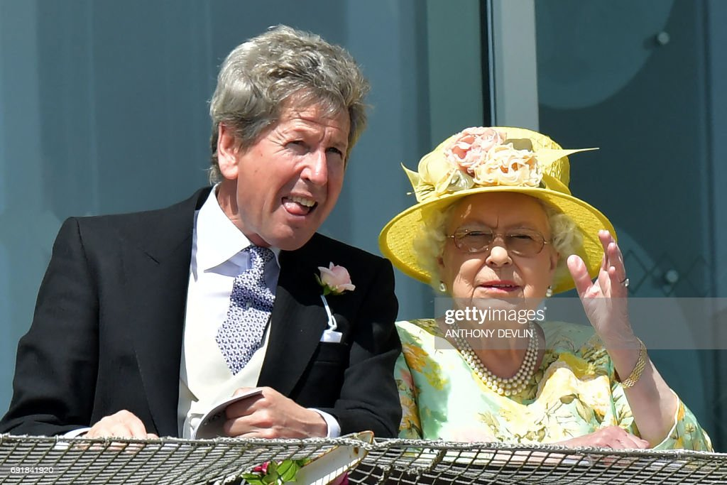Britain's Queen Elizabeth II (R) and the Queen's racing manager, John Warren watch the racing on the second day of the Epsom Derby Festival in Surrey, southern England on June 3, 2017.