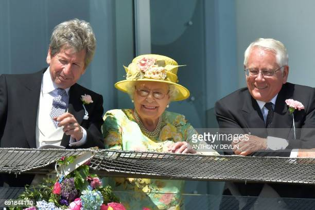 Britain's Queen Elizabeth II and the Queen's racing manager, John Warren watch the racing on the second day of the Epsom Derby Festival in Surrey,...