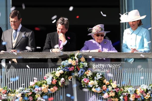 Britain's Queen Elizabeth II and the Queen's racing manager John Warren attend the second day of the Epsom Derby Festival in Surrey southern England...