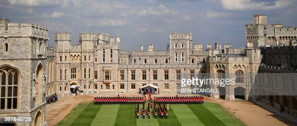Britain's Queen Elizabeth II and US President Donald Trump and US First Lady Melania Trump stand on the dias facing an honour guard formed of...