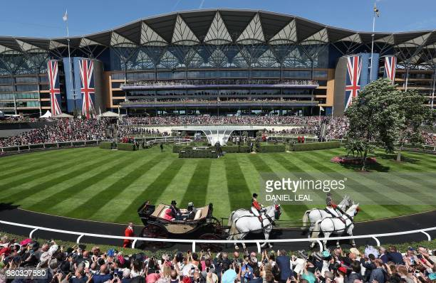 Britain's Queen Elizabeth II arrive by horsedrawn carriage as she attends Ladies Day at the Royal Ascot horse racing meet in Ascot west of London on...
