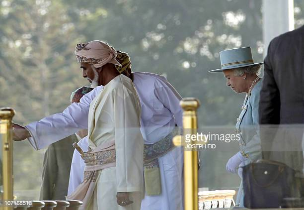 Britain�s' Queen Elizabeth II arrive with Oman�s leader Sultan Qaboos bin Said as they attend an equestrian show at Madinat alHidayat on November 27...