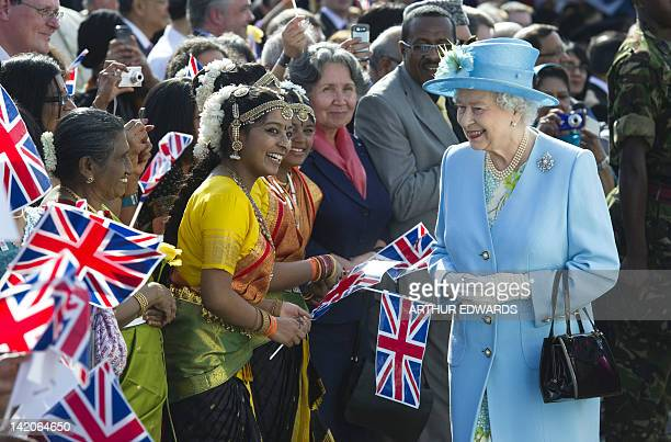 Britain's Queen Elizabeth II arrives and greets flagwaving wellwishers at the Krishna Avanti school in Harrow north London on March 29 2012 The visit...