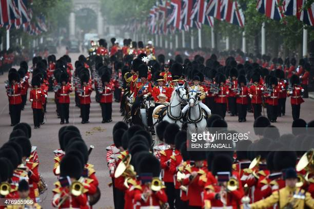 Britain's Queen Elizabeth II arrives back at Buckingham Palace from Horse Guards Parade in a horsedrawn carriage preceeded and followed by marching...