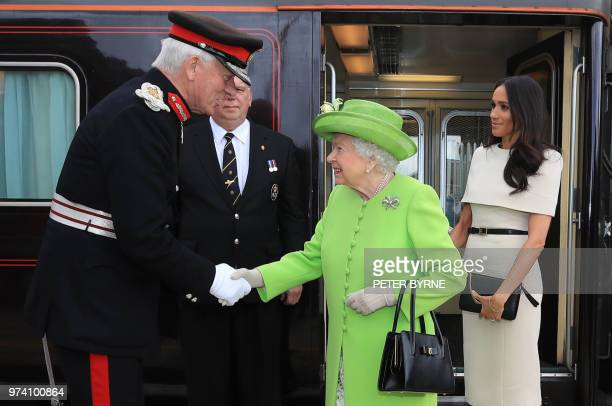 Britain's Queen Elizabeth II arrives with Meghan Duchess of Sussex by Royal Train at Runcorn Station to carry out engagements in Cheshire on June 14...