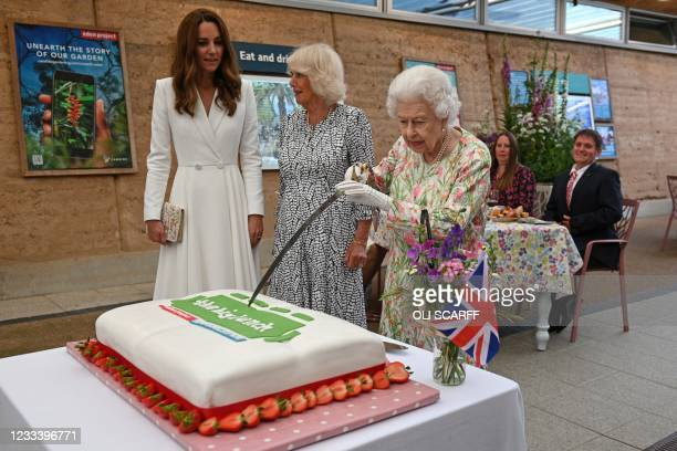 Britain's Queen Elizabeth II attempts to cut a cake with a sword, lent to her by The Lord-Lieutenant of Cornwall, Edward Bolitho, to celebrate of The...