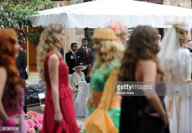 Britain's Queen Elizabeth II attends a banquet and fashion show at a silk market with Turkish designer Rifat Ozbek in Turkey's northwest city of...