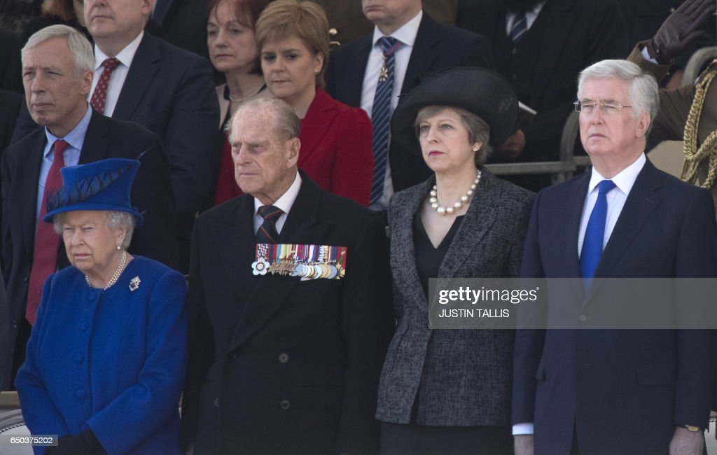 Britain's Queen Elizabeth II (L), Britain's Prince Philip, Duke of Edinburgh (2nd L), British Prime Minister Theresa May (2nd R) and British Defence Secretary Michael Fallon (R) attend a Service of Commemoration and Drumhead Service on Horse Guards Parade in central London on March 9, 2017, which honours the service and duty of both the UK Armed Forces and civilians in the Gulf region, Iraq and Afghanistan, and those who supported them back home, from 1990-2015. After the Drumhead Service, The Queen will officially unveil The Iraq and Afghanistan memorial. / AFP PHOTO / Justin TALLIS
