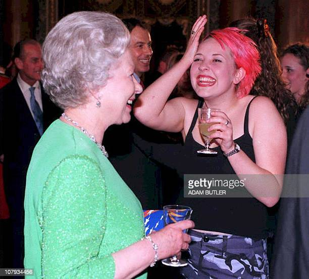 Britain's Queen Elizabeth II chats with Julie Thompson , a vocalist with the first rock band to perform at Buckingham Palace 03 April. The...