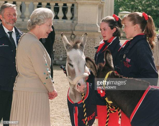 Britain's Queen Elizabeth II chats with Rachel Dancer from Telford, Shropshire, and Holly Smith from Sheffield, 12 June, and their donkeys Joshua and...