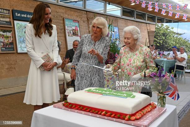 Britain's Queen Elizabeth II considers cutting a cake with a sword, lent to her by The Lord-Lieutenant of Cornwall, Edward Bolitho, to celebrate of...