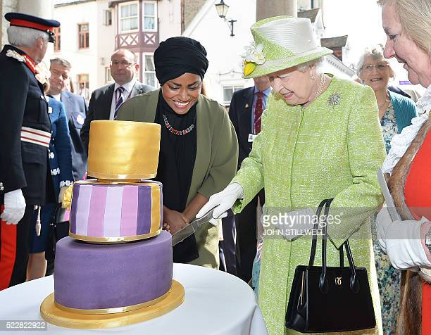 Britain's Queen Elizabeth II cuts into a cake made by Nadiya Hussein winner of the Great British Bake Off during a 'walkabout' on her 90th birthday...