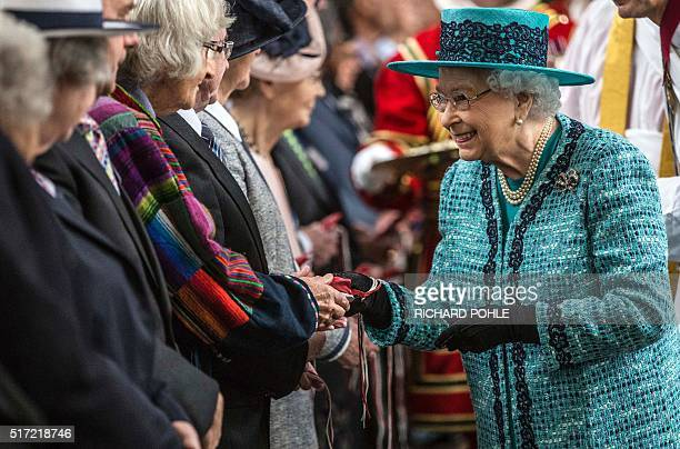 Britain's Queen Elizabeth II distributes Maundy money during the Royal Maundy Service at St George's Chapel in Windsor west of London on March 24...