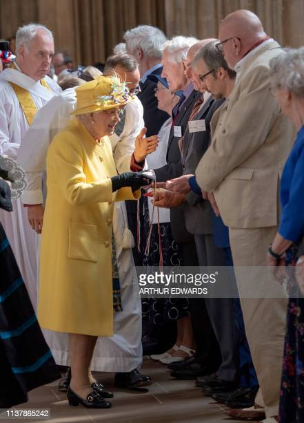 Britain's Queen Elizabeth II distributes the Maundy money during the Royal Maundy Service at St George's Chapel in Windsor west of London on April 18...