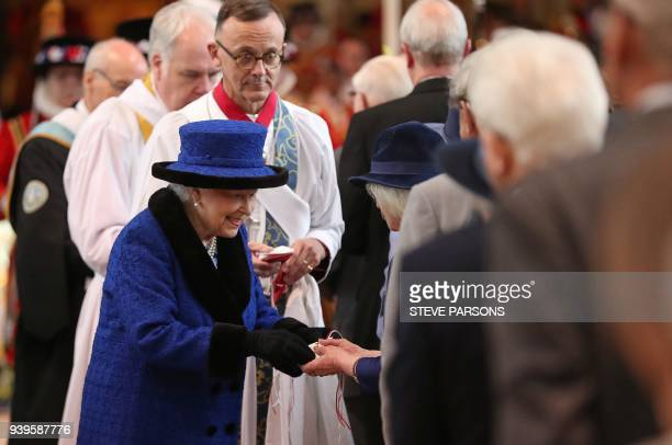 Britain's Queen Elizabeth II distributes the Maundy money during the Royal Maundy Service at St George's Chapel in Windsor west of London on March 29...