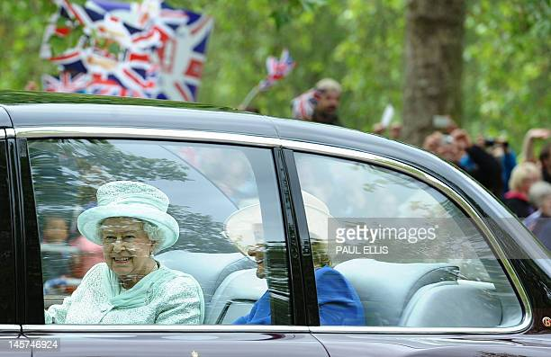 Britain's Queen Elizabeth II drives down the Mall with Diana Marion The Lady Farnham on her way to Saint Paul's Cathedral during the Queen's Diamond...