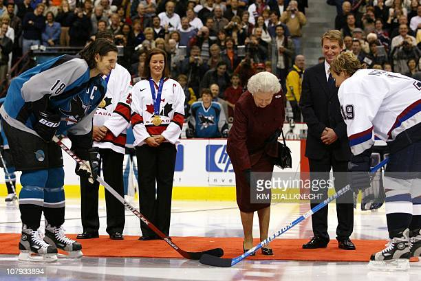 Britain's Queen Elizabeth II drops the ceremonial puck prior to the Vancouver Canucks preseason game against the San Jose Sharks 06 October 2002 in...