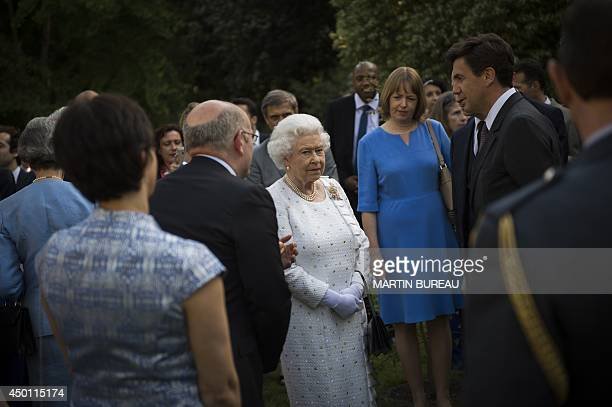 Britain's Queen Elizabeth II flanked by Britain Ambassador to France Sir Peter Ricketts shakes hands with Sir Bradley Wiggins winner of the 2012...