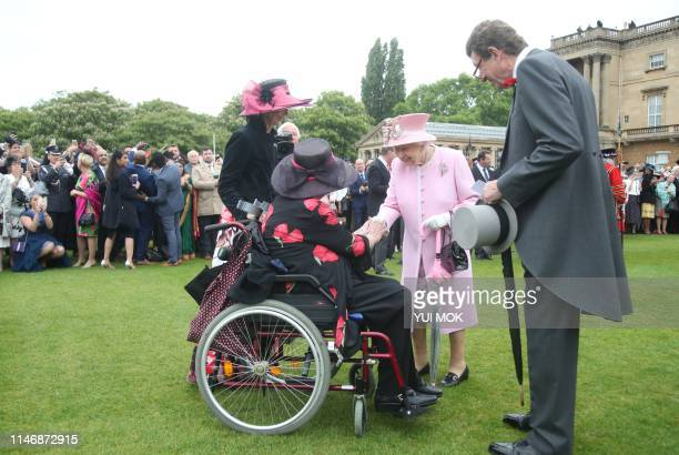 Britain's Queen Elizabeth II gestures as she meets guests at the Queen's Garden Party in Buckingham Palace central London on May 29 2019