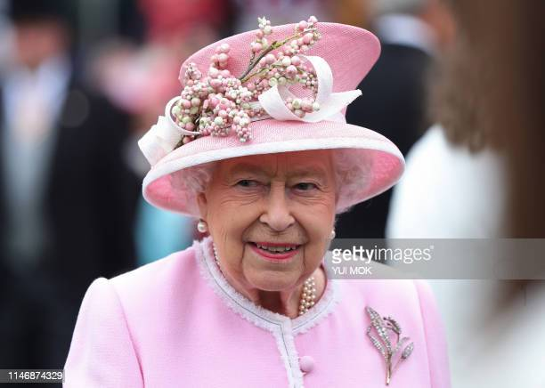 Britain's Queen Elizabeth II gestures as she meets guests at the Queen's Garden Party in Buckingham Palace, central London on May 29, 2019.