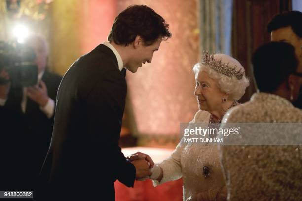 TOPSHOT Britain's Queen Elizabeth II greets Canada's Prime Minister Justin Trudeau in a receiving line in the Blue Drawing Room for a drinks...