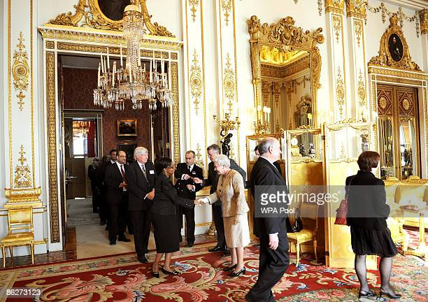 Britain's Queen Elizabeth II greets guests as she hosts a reception to mark the 60th anniversary of the Commonwealth at Buckingham Palace on April 28...