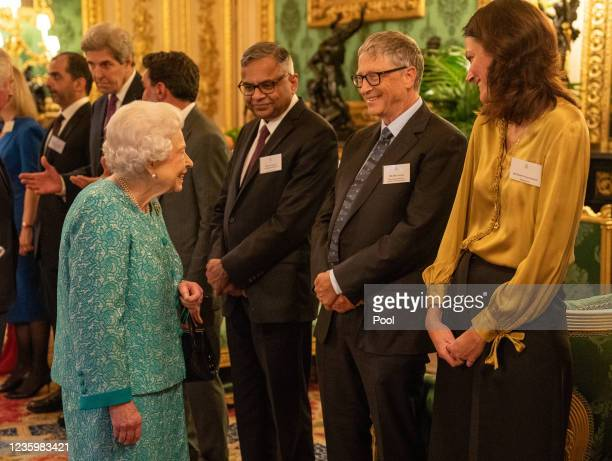 Britain's Queen Elizabeth II greets Microsoft co-founder turned philanthropist Bill Gates and Darktrace's co-founder and CEO Poppy Gustafsson during...