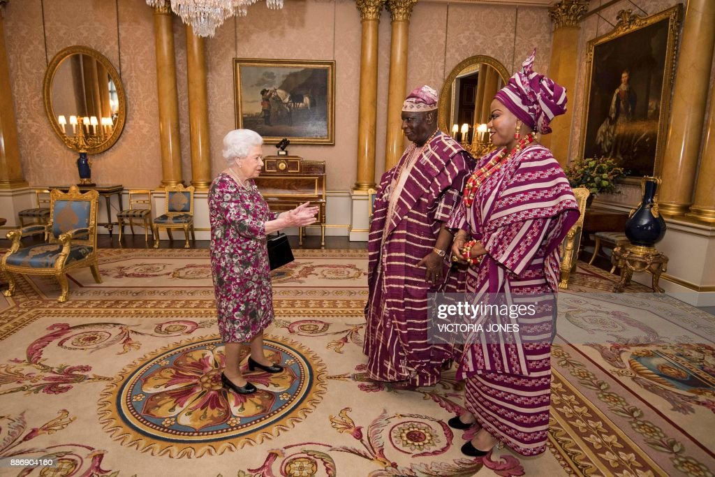 TOPSHOT - Britain's Queen Elizabeth II (L) greets Nigeria's ambassador to the United Kingdom, George Adesola Oguntade (C), and his wife, Modupe Oguntade, during a private audience at Buckingham Palace in central London, on December 6, 2017. / AFP PHOTO / POOL / Victoria Jones