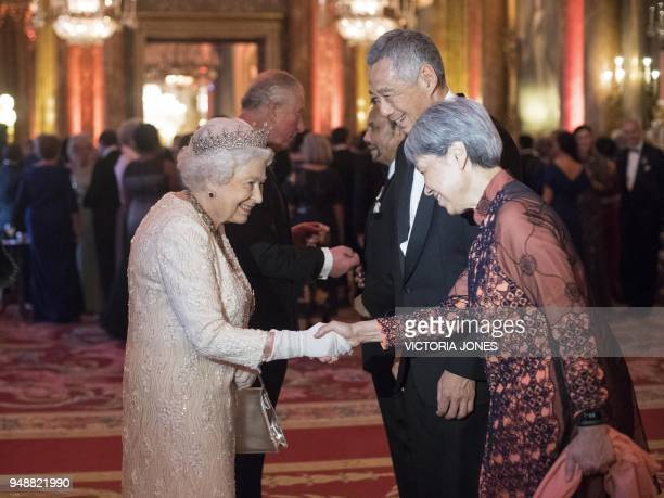 Britain's Queen Elizabeth II greets Singapore's Prime Minister Lee Hsien Loong and his wife Ho Ching in the Blue Drawing Room during a drinks...