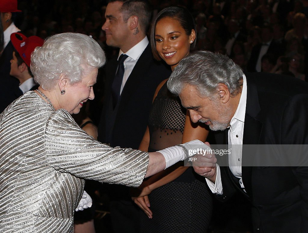 Britain's Queen Elizabeth II (L) greets Spanish tenor Placido Domingo (R) after the Royal Variety Performance at the Royal Albert Hall in London on November 19, 2012. The Queen, accompanied by The Duke of Edinburgh, attended the Royal Variety Performance in the show's 100th anniversary year where she met with stars of the show including Kylie Minogue, tenor Andrea Bocelli and the performing dog Pudsey.