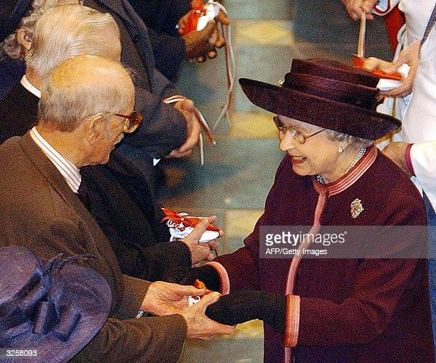 Britain's Queen Elizabeth II hands out maundy money during the Royal Maundy Service held at Liverpool's Anglican Cathedral 08 April 2004 Traditional...