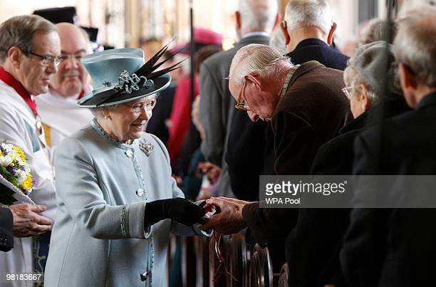 Britain's Queen Elizabeth II hands out Maundy money to pensioners at the Maunday service at Derby Cathedral on April 1 2010 in Derby United Kingdom...