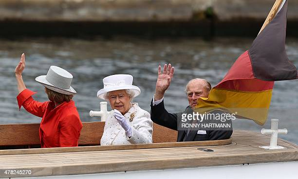 Britain's Queen Elizabeth II her husband Prince Philip The Duke of Edinburgh and partner of the German President Daniela Schadt wave during a boat...