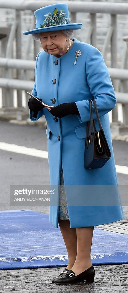 Britain's Queen Elizabeth II hold a pair of scissors after cutting a ribbon at the official opening ceremony for the Queensferry Crossing, a new road bridge spanning the Firth of Forth from Queensferry to North Queensferry, in Queensferry, west of Edinburgh, on September 4, 2017. The new crossing, which is the longest three-tower, cable-stayed bridge in the world, and unlike the existing bridge, is expected to remain open in all weathers. /