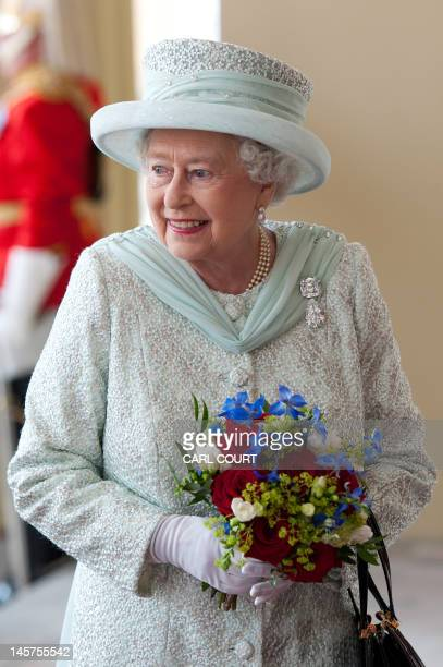 Britain's Queen Elizabeth II holds a bouquet of flowers as she returns to Buckingham Palace after attending a National Service of Thanksgiving and a...