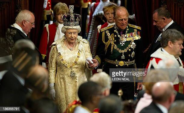 Britain's Queen Elizabeth II holds the hand of her husband Prince Philip, as she arrives to address to the House of Lords, during the State Opening...