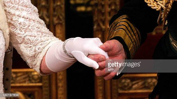 Britain's Queen Elizabeth II holds the hand of the Duke of Edinburgh after delivering her speech to the House of Lords at the Palace of Westminster...