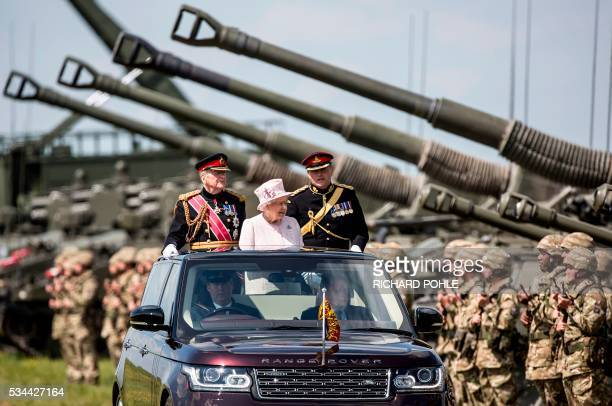 Britain's Queen Elizabeth II , in her role as Captain-General of The Royal Regiment of Artillery, stands in the State Review Range Rover as she...