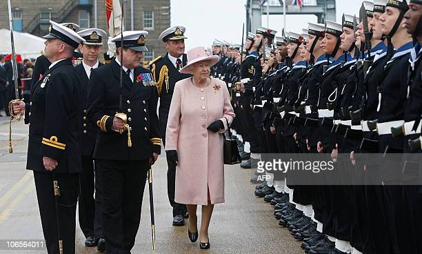 Britain's Queen Elizabeth II inspects a Naval Guard of Honour formed on the quayide where HMS Ark Royal is moored in Portsmouth southern England on...