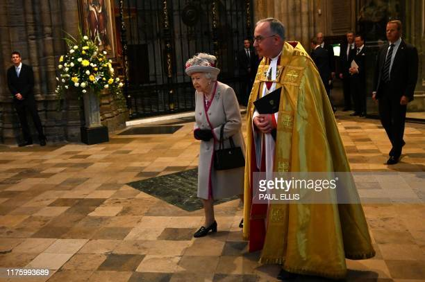 Britain's Queen Elizabeth II is accompanied by Dean of Westminster John Hall on her arrival to attend a service to mark the 750th anniversary of...