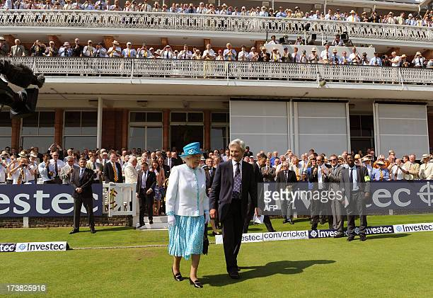 Britain's Queen Elizabeth II is applauded as she walks onto the field to meet England and Australian players at Lord's cricket ground before the...