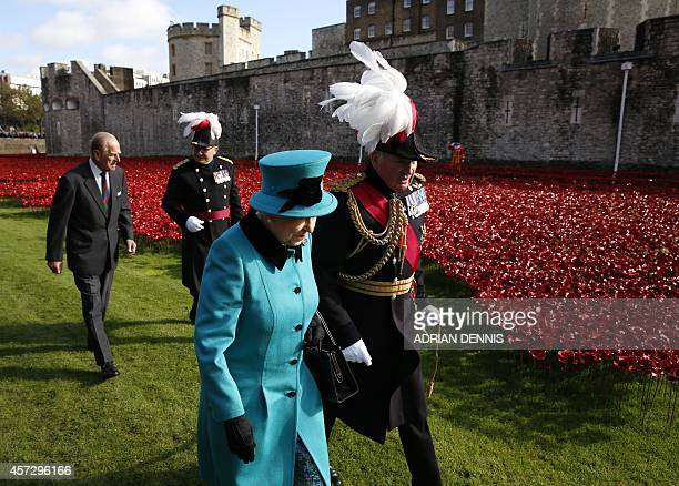 Britain's Queen Elizabeth II is escorted past the poppies as she and her husband Prince Philip visit the Tower of London's 'Blood Swept Lands and...