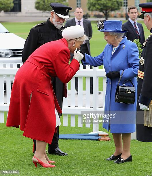 Britain's Queen Elizabeth II is greeted by Prince and Princess Michael of Kent during a visit to the Honourable Artillery Company in London on June 1...