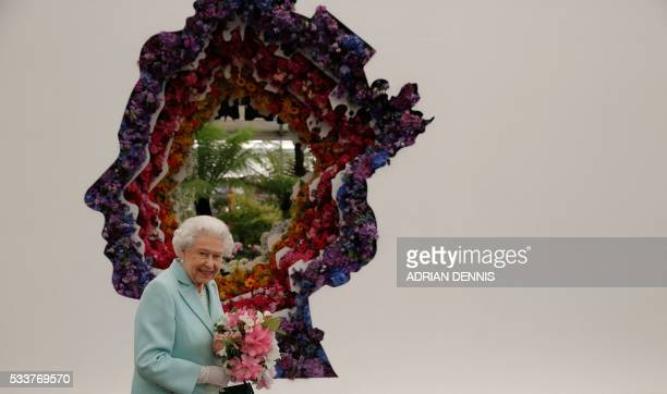 Britain's Queen Elizabeth II is pictured beside a floral exhibit by the New Covent Garden Flower Market which features an image of the Queen during a...
