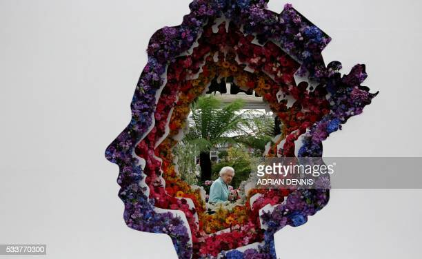 Britain's Queen Elizabeth II is pictured through a gap in a floral exhibit by the New Covent Garden Flower Market, which features an image of the...