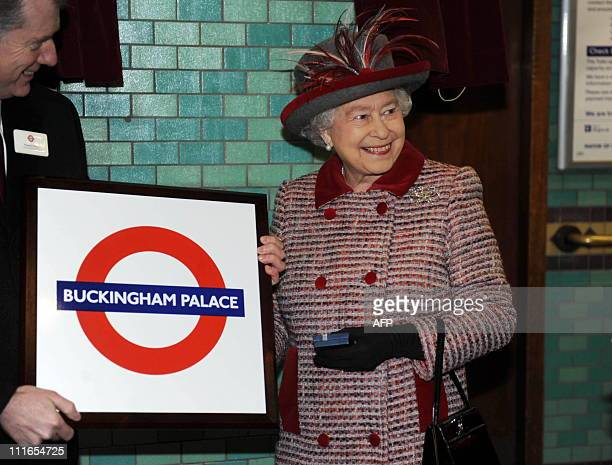 Britain's Queen Elizabeth II is presented with a tube station sign for Buckingham Palace during a visit to Aldgate Underground station in London on...
