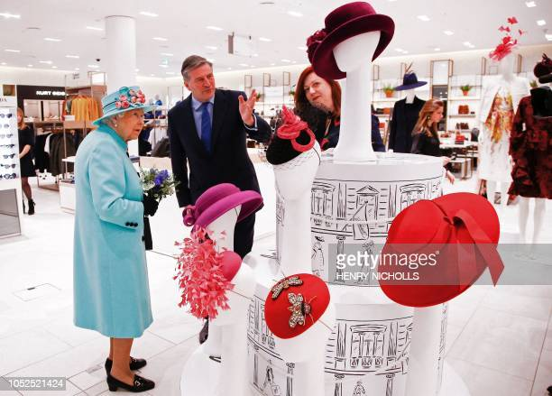 TOPSHOT Britain's Queen Elizabeth II is shown a display of hats as she tours Fenwicks department store at The Lexicon shopping centre during a visit...